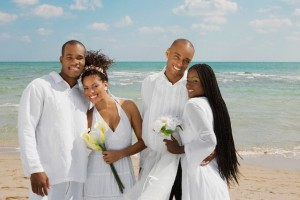 Multi-ethnic newlyweds hugging at beach