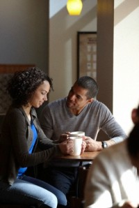 Mixed race couple having coffee in cafe