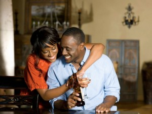 Young woman embracing man holding beer bottle, smiling